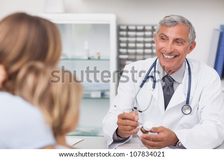 Smiling doctor writing on a drug box in a medical office - stock photo