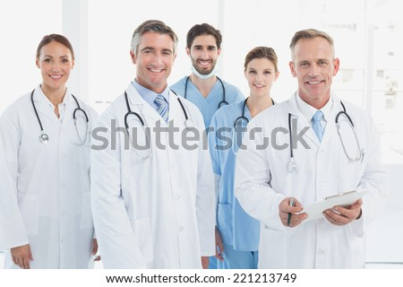 Smiling doctors all standing together as they work - stock photo