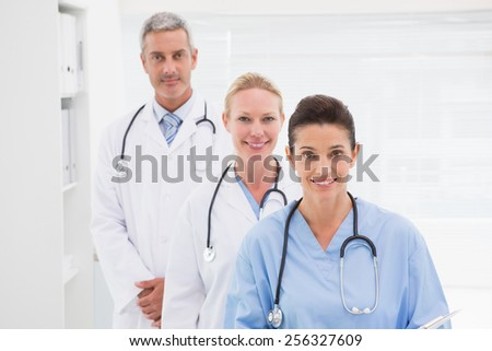 Smiling doctors looking at camera in medical office - stock photo