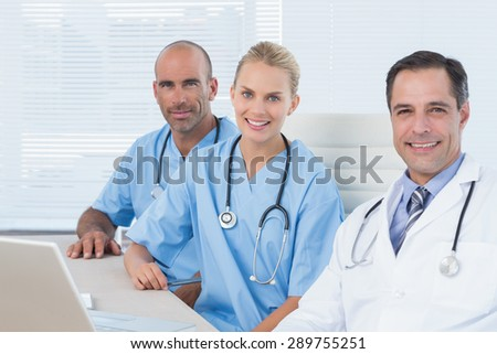 Smiling doctors looking at camera with his colleagues in medical office - stock photo