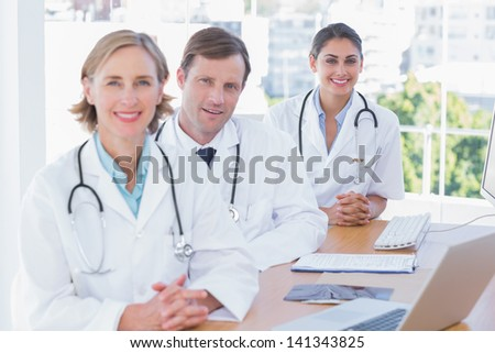 Smiling doctors posing at their desk with a laptop computer