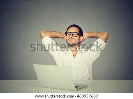 Smiling dreaming young man in glasses looking up while working at laptop computer. Happy guy relaxing after working hard at his office table