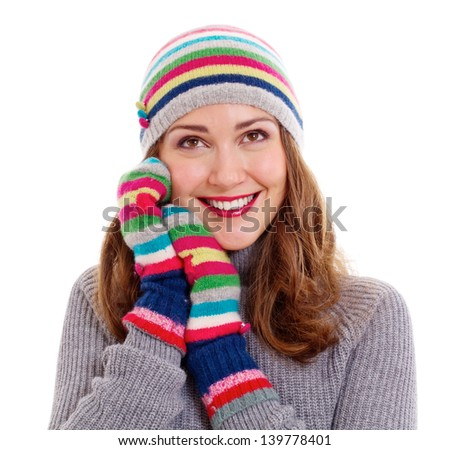 Smiling dreamy girl in colorful cap and mittens. Isolated on white background, mask included