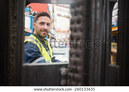 Smiling driver operating forklift machine in warehouse - stock photo