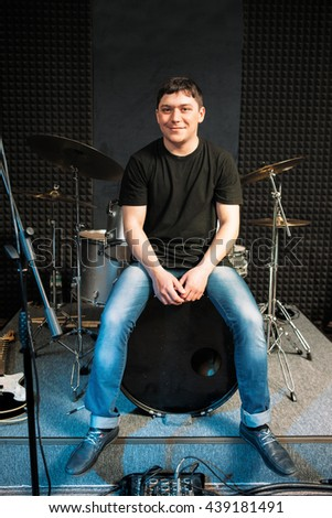 Smiling drummer sitting on the drum. Guy sitting on big drum smiles at camera. Young smiling drummer in casual clothes at music studio - stock photo