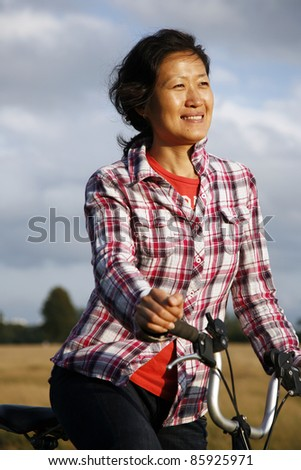 Smiling East Asian Woman Cycling in Richmond Park at Dusk - stock photo