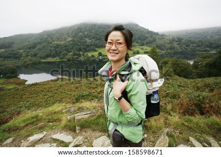Smiling East Asian Woman hiking in Lake District, Cumbria, UK.