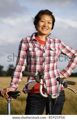 Smiling East Asian Woman Looking the Camera in Richmond Park with Bicycle at Dusk - stock photo