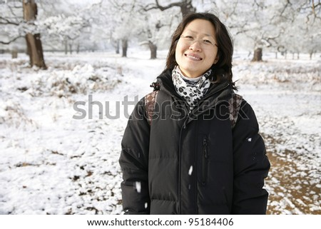 Smiling East Asian Woman Looking the Camera in snow covered Richmond Park