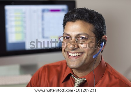 Smiling East Indian customer service rep with headset and computer monitor