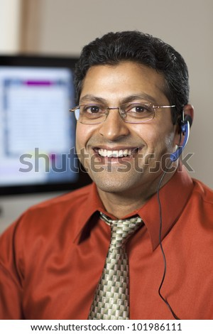 Smiling East Indian customer service representative with headset and computer monitor - stock photo