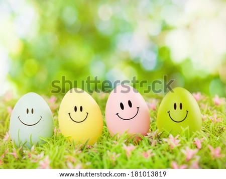 smiling easter eggs outdoor in green - stock photo