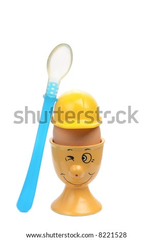 Smiling eggcup with a helmet and the blue spoon - stock photo