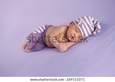 Smiling eight day old newborn baby girl sleeping peacefully. She is wearing a striped, lilac and white, upcycled sleeping cap and pant set. - stock photo
