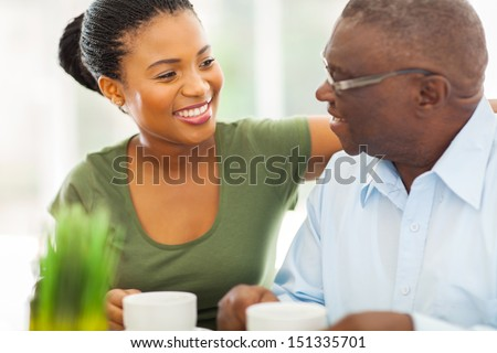 smiling elderly african american man enjoying coffee with his granddaughter at home - stock photo