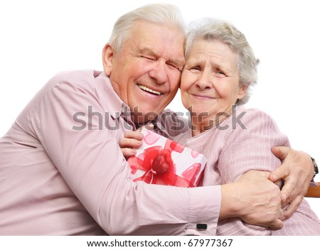 smiling elderly couple and box with gift on white background