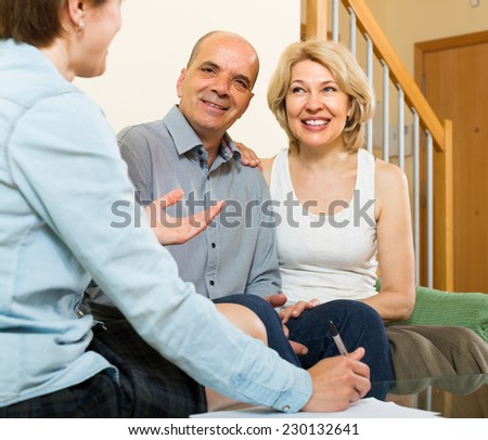 Smiling elderly couple filling questionnaire for employee in the living room  - stock photo