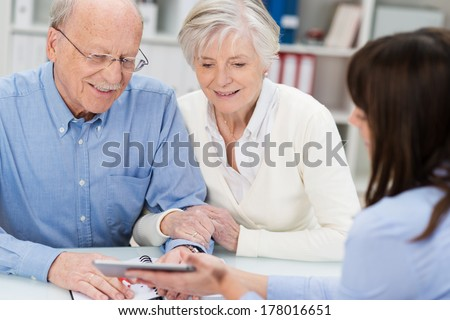 Smiling elderly couple receiving financial advice from a female broker who is showing them a calculator