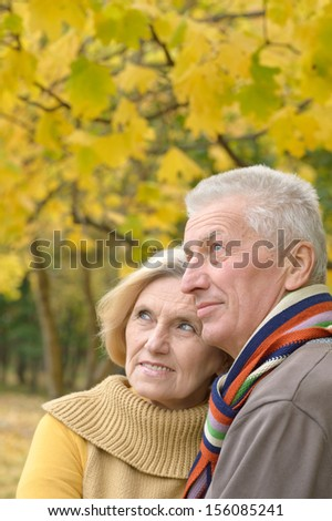 Smiling elderly couple resting in autumn park