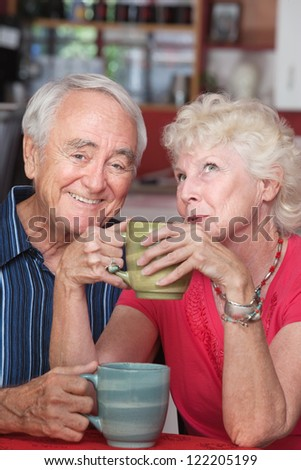 Smiling elderly couple with mugs at a coffeehouse - stock photo