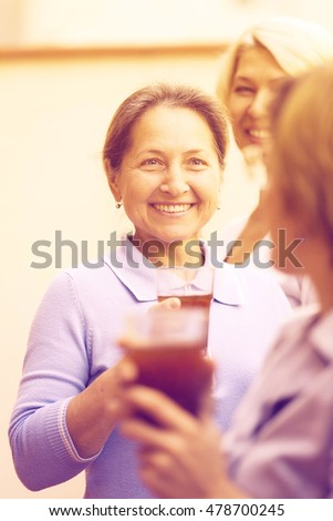Smiling elderly female colleagues having lunch break at patio