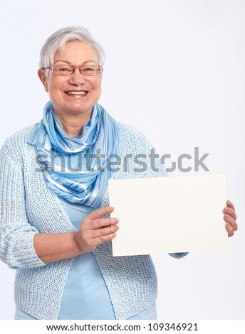 Smiling elderly lady holding blank sheet in hand, looking at camera. - stock photo