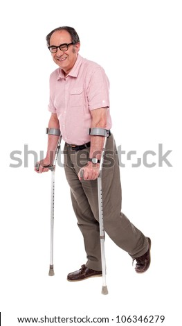 Smiling elderly man with crutches over white background - stock photo
