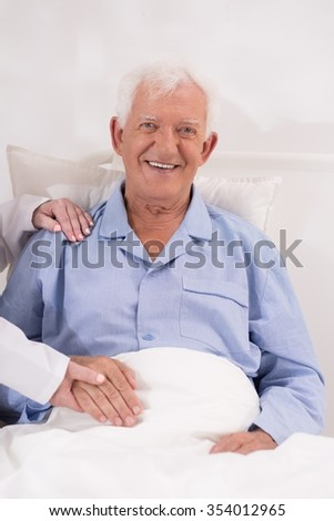 Smiling elderly patient sitting in hospital bed - stock photo