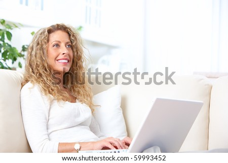 Smiling elderly senior woman with laptop at home
