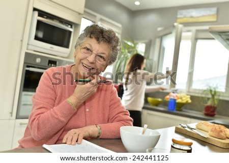 Smiling elderly woman at home with homecare - stock photo