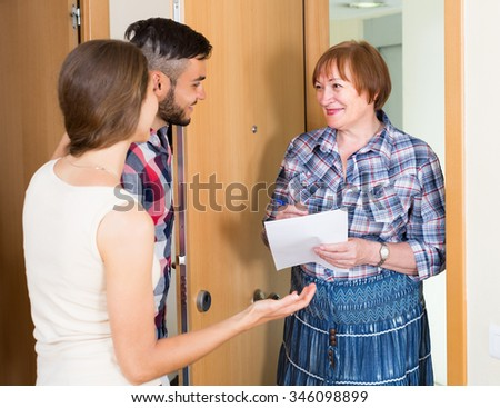 Smiling elderly woman conducting survey among neighbours at the door - stock photo