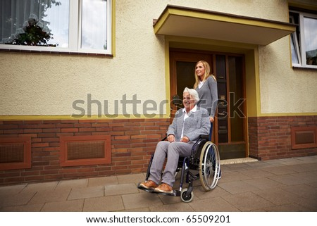 Smiling elderly woman in front of a retirement home - stock photo