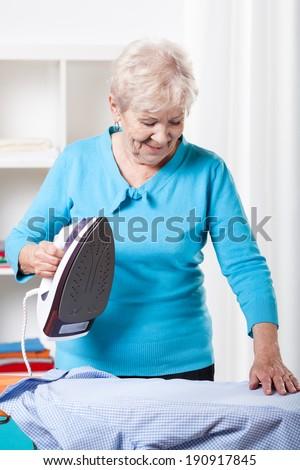 Smiling elderly woman ironing blue shirt at home - stock photo