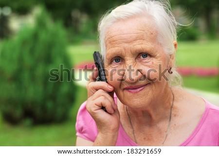 Smiling elderly woman senior portrait on the phone - stock photo