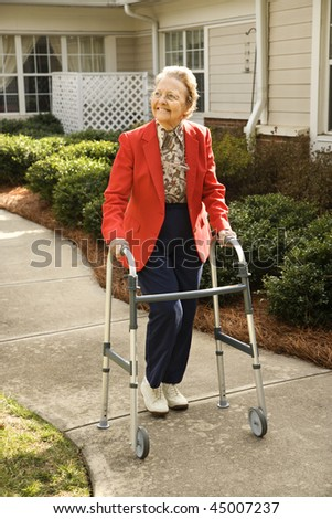 Smiling elderly woman takes a stroll outdoors with her walker.  Vertical shot.
