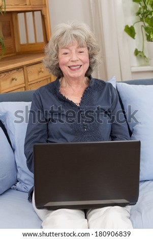 Smiling elderly woman with laptop on her lap