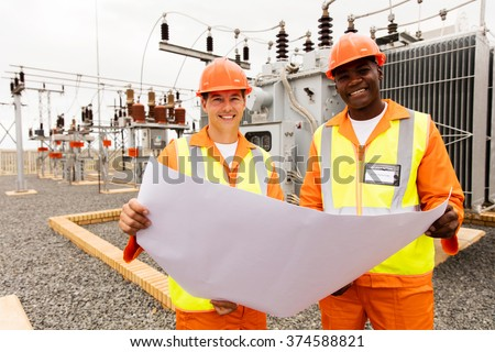 smiling electricians holding blueprint at substation - stock photo