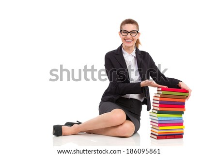 Smiling elegance woman sitting on the floor close to stack of books. Full length studio shot isolated on white. - stock photo
