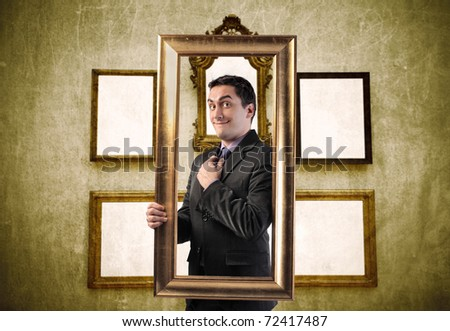 Smiling elegant man holding a frame with empty frames on the background - stock photo