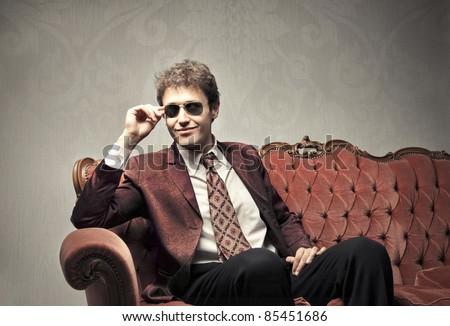 Smiling elegant man sitting on a velvet sofa - stock photo