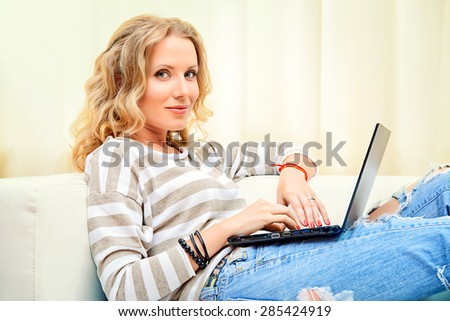 Smiling elegant woman sitting on a sofa with her laptop computer. Home interior, furniture. Lifestyle. - stock photo