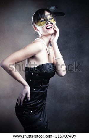smiling elegant young woman with mask studio shot - stock photo