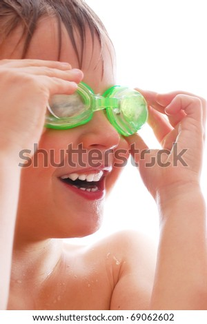 smiling elementary age boy  with wet hair and goggles laughing - stock photo