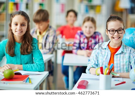Smiling elementary school kids sitting at desks in classroom