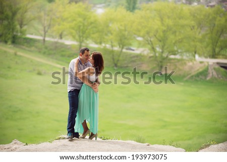 smiling embracing couple on steep - stock photo