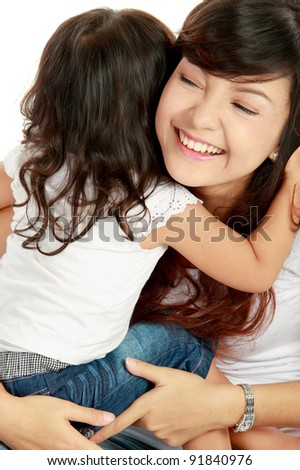 Smiling embracing mom and daughter isolated over white background - stock photo