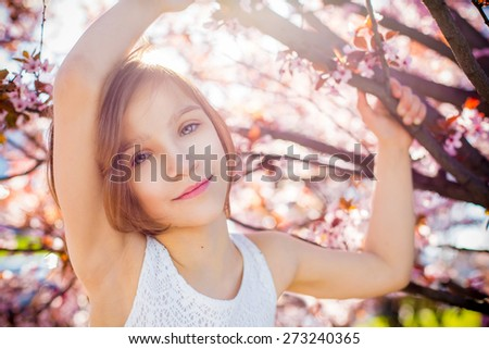 smiling emotional cute adorable baby girl portrait in blossom pink flowers tree art beauty - stock photo