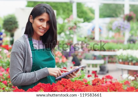 Smiling employee using tablet pc to check red flowers in garden center - stock photo