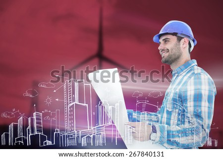 Smiling engineer looking away while holding blueprint against windmill spinning over a green field