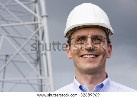 Smiling engineer with hardhat on construction site - stock photo
